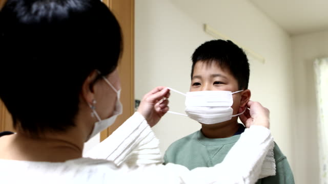 son getting a mask from mother to prevent illness - 予防点の映像素材/bロール