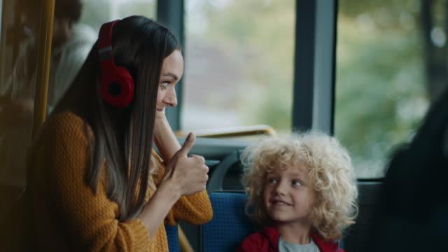 sohn gibt kopfhörer an mutter, so dass sie eine musik im bus hören kann - unterwegs stock-videos und b-roll-filmmaterial