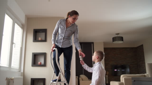 son helping mother to change a lightbulb - improvement stock videos & royalty-free footage
