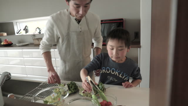 son is serve the salad together the father - domestic kitchen stock videos & royalty-free footage