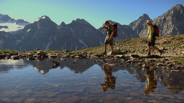 MS, PAN, son (12-13) leading mother across mountain stream, Banff National Park, Alberta, Canada