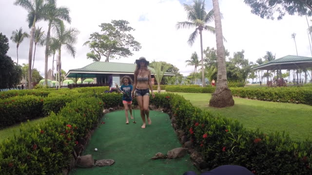 son picks up golf ball and mother and daughter jog down the mini golf course at resort. - minigolf stock-videos und b-roll-filmmaterial