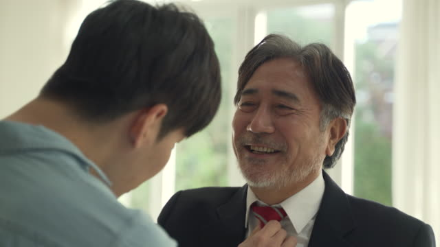 son puts on a tie to his father - son stock-videos und b-roll-filmmaterial