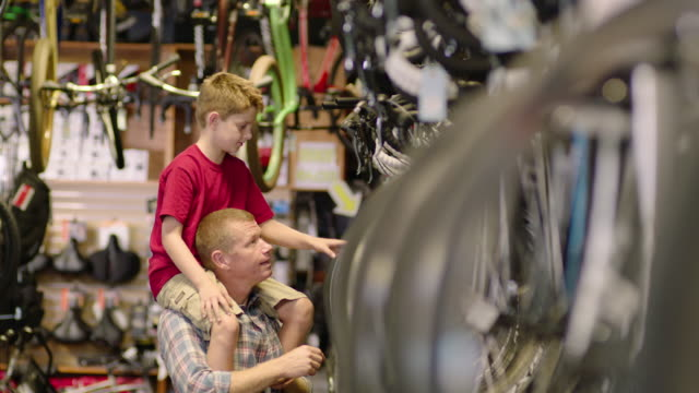 Son riding on dad's shoulders looks around bike shop in wonder