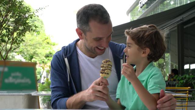 vídeos de stock, filmes e b-roll de filho de partilha com o pai de um picolé no ice cream parlor - sorvete