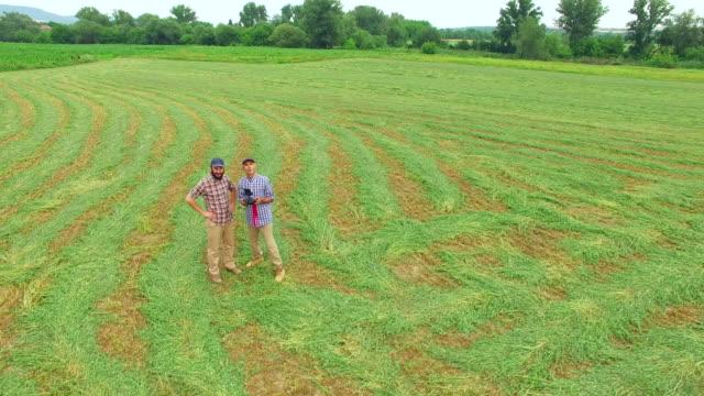 息子は、ストリップフィールドでリモートコントロールでドローンを飛ばすために父農家を示しています - 農学者点の映像素材/bロール