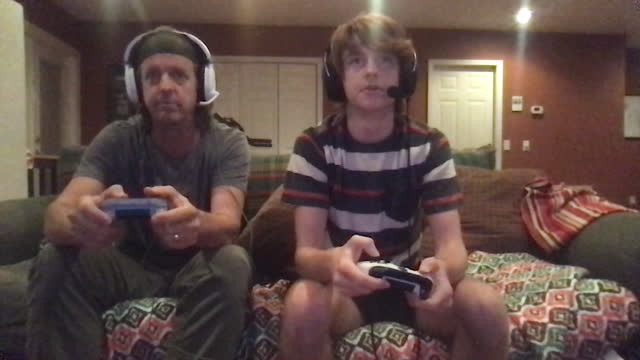 son teaches his dad how to play multiplayer online video games on their couch - single father stock videos & royalty-free footage