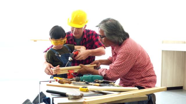 vidéos et rushes de fils utiliser cordless screwdriver drill avec l'aide de grand-père et de père - bricolage