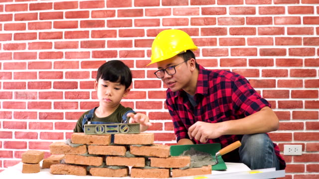 son use level to make brick having level by himself with construction father's help on a new house - stone material stock videos and b-roll footage