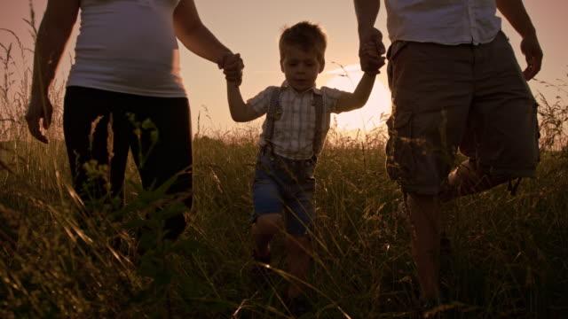 SLO MO Son walking through the high grass