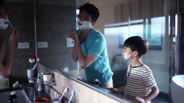 stockvideo's en b-roll-footage met zoon kijken vader scheren baard - gootsteen
