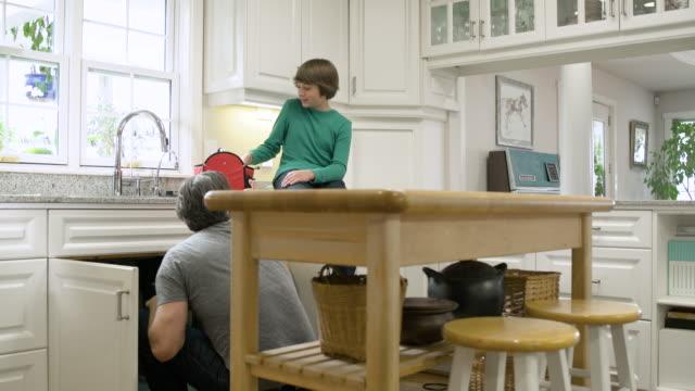 son watching his father working under kitchen sink - キッチンシンク点の映像素材/bロール