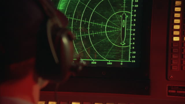 A sonar screen tracks a missile targeting a submarine.