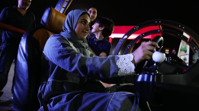 sondos ashi tries out a car driving simulator as members of her family look on during an outdoor educational driving event for women on june 21 2018... - censura video stock e b–roll