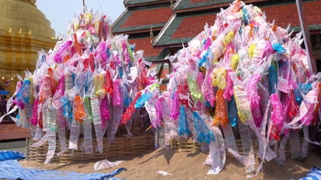 vídeos y material grabado en eventos de stock de songkran festival tailandia, bandera tradicional decorada en la arena pila en wat para que hariphunchai en lamphun - arte decorativo