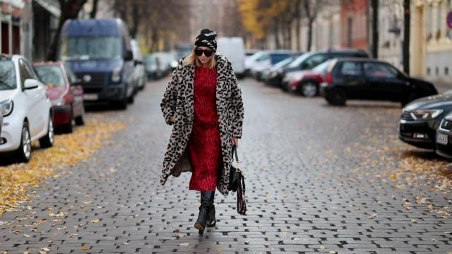 Sonia Lyson is seen wearing black leather boots Zara red leo dress Zara black white leo coat Max Mara sunglasses vintage Balenciaga beanie Dior...