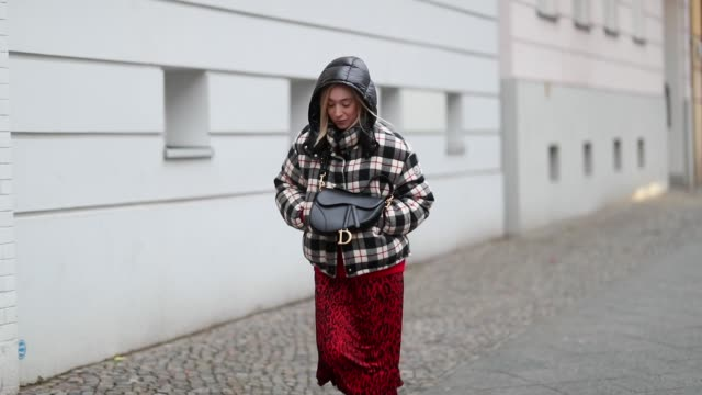 Sonia Lyson is seen wearing olive green boots Dior red dress Zara with animal print plaid Moncler jacket Dior saddle bag during the Berlin Fashion...
