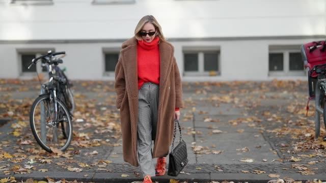 Sonia Lyson is seen wearing orange sneakers Adidas Yun plaid chinos Zara red neon turtleneck Zara brown teddy coat Max Mara sunglasses Chimi eyewear...