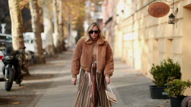 stockvideo's en b-roll-footage met sonia lyson is seen wearing snake boots zara pleated skirt max co turtleneck zara brown shearling jacket ducie golden vintage bag gucci dior... - jak jas