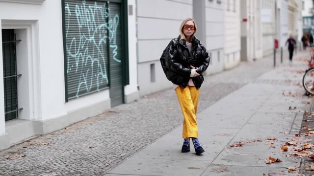 vídeos de stock e filmes b-roll de sonia lyson is seen wearing yellow velvet pants, striped knit &other stories, black down feather jacket pyrenex, trekking boots edited, yellow... - casaco curto com mangas