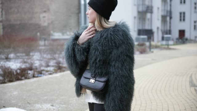 Sonia Lyson wearing a black beanie other stories waxed pants Zara Gucci sneakers knit Acne a green fluffy sheep fur jacket from Meotine on January 18...