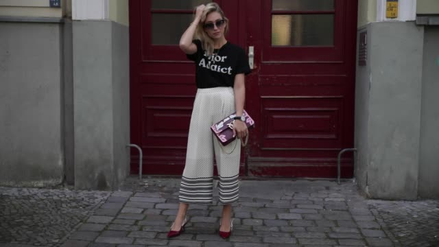 vídeos de stock e filmes b-roll de sonia lyson wearing a black dior tshirt with the print dior addict cropped wide leg topshop pants a pinko bag with the print love me tender dior... - sapato aberto atrás