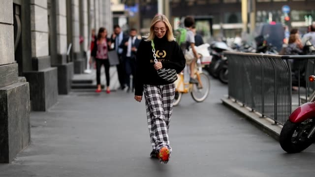 sonia lyson wearing checked pants, sweater, fanny bag balenciaga, orange adidas sneakers, sunglasses is seen during milan fashion week spring/summer... - scarpe da ginnastica video stock e b–roll