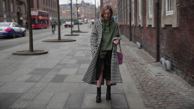sonia lyson wearing oversized sweatshirt - topshop, duster coat, checked - topshop, vinyl skirt - h&m trend, mesh tights - calzedonia, boots - zara,... - カルツェドニア点の映像素材/bロール
