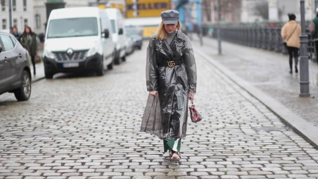Sonia Lyson wearing raincoat plastic trench coat Asos Miu Miu shoes green pants Urban Outfitters Gucci belt flat cap Topshop Fendi bag earrings Wald...
