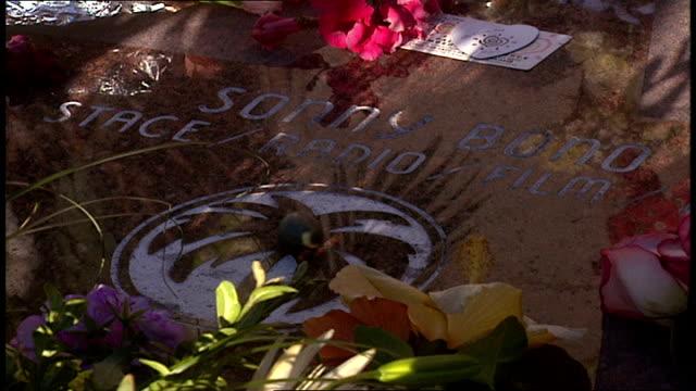 vidéos et rushes de sonny bono plaque flowers and items left for memorial in palm springs california - plaque rue
