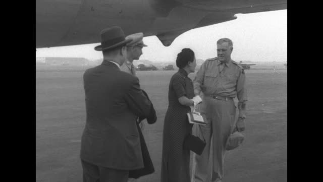 soong meiling aka madame chiang kaishek stands with two american military officers and a chinese aide they shake hands and she climbs boarding stairs... - airplane tail stock videos and b-roll footage