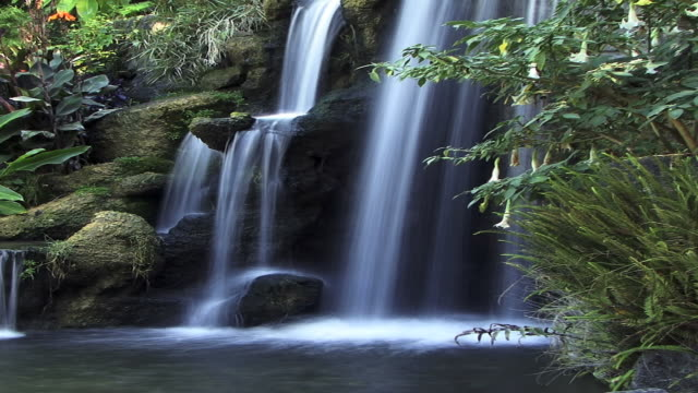 a soothing waterfall into a pond. - digital enhancement stock videos and b-roll footage