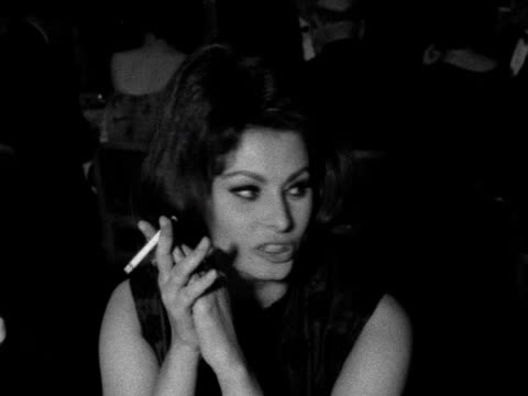 sophia loren laughs and smokes a cigarette at the british film academy awards. 1961. - academy awards video stock e b–roll