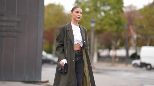 stockvideo's en b-roll-footage met sophia roe wears a green long coat a black leather chanel bag a white cropped shirt black denim jeans chanel pointy shoes outside chanel during paris... - modeweek