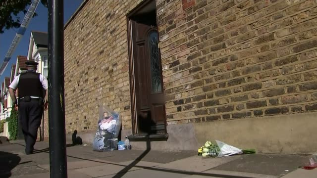 Ouissem Medouni accuses partner Sabrina Kouider R220917003 / Southfields Floral tribute on pavement and police officer standing nearby Close shot of...