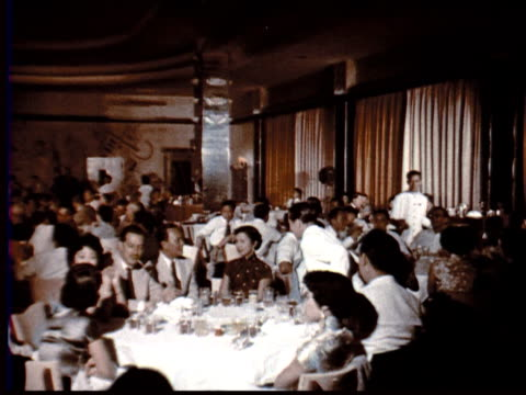 1957 MONTAGE Sophisticated Chinese restaurant. Well dressed Chinese + western diners at table. Chinese female cabaret singer at microphone. Couples dancing / Singapore / AUDIO