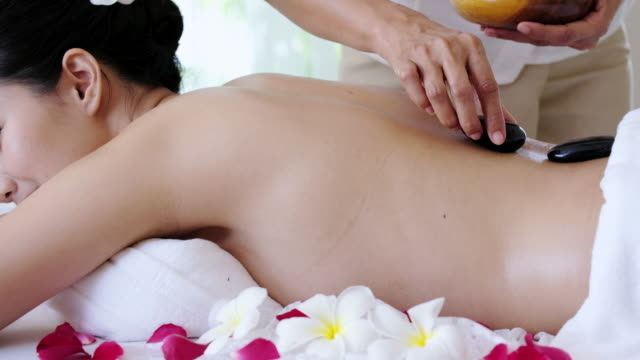 Sophisticated Spa Treatment and massage for relaxation,Young woman receiving back spa hot stone