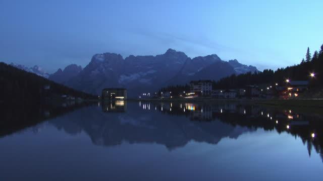 ws, sorapis mountains and buildings reflected in lake misurina at dusk, dolomites, alps, italy - tonad bild bildbanksvideor och videomaterial från bakom kulisserna
