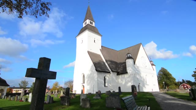vidéos et rushes de sorunda sweden beautiful white church and cemetery in small picturesque town south of stockholm - suède