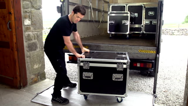 Sound engineer unloads Flight case from the back of a Truck