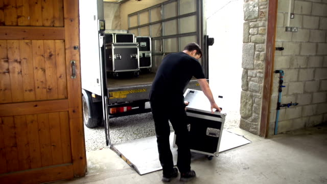 sound technician unloads flightcase and sound equipment from truck - flight case stock videos and b-roll footage