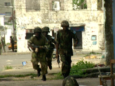 Sounds of sporadic shooting as ECOMOG soldiers take cover by buildings Monrovia 1997