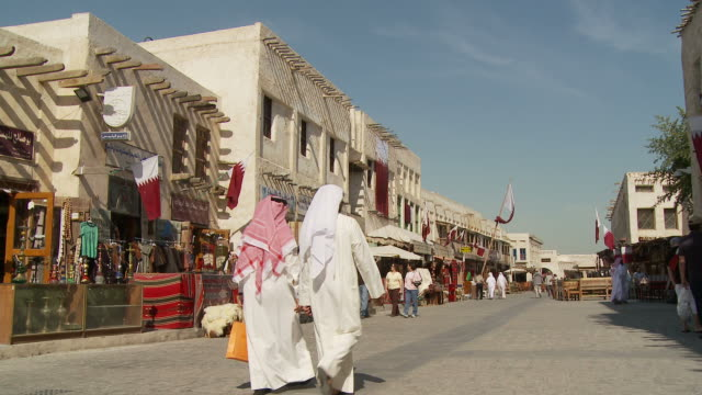 ws souq waqif with market stalls and qatari flags on building / doha, qatar - souk stock videos & royalty-free footage