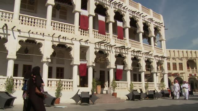 vídeos de stock e filmes b-roll de ws souq waqif with qatari flag on building / doha, qatar - doha