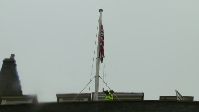 stockvideo's en b-roll-footage met british victims named reactions and condolences england london ext man lowering union jack flag above downing street zoom in flag hanging at half mast - laten zakken