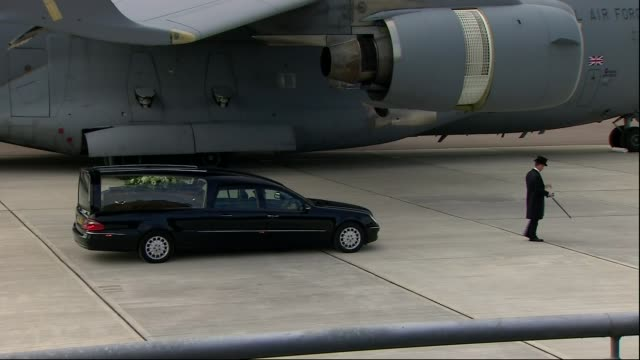 police arrests / further bodies returned to uk hearse carrying coffin of british victim along slowly from c17 cargo plane - carro funebre video stock e b–roll