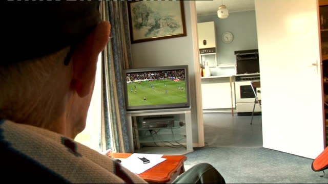 england final squad announced les white wearing aston villa scarf and cap as sits in armchair watching plasma screen colour television white... - neckwear stock videos and b-roll footage