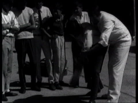 South Africa readmitted to Olympics ITN LIB B/W 1960s Johannesburg MS Basil D'Oliveira demonstrating strokes to young Asian boys looking on CS Child...