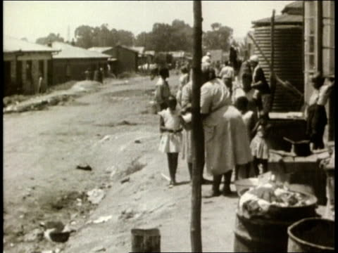 south african black township / large shantytown and poor people outside their shacks / young nelson mandela walking down township alley with a white... - racism stock videos and b-roll footage