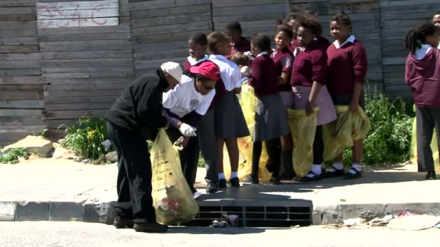 South African Nobel Prize winner Desmond Tutu joins a group of volunteers to clean up the Joe Slovo informal settlement near his home in the...